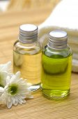 Spa and beauty treatment -bottles with essential oils and towel on bamboo stick straw mat