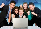 stock photo of business-office  - Business success team in an office in front of a laptop computer - JPG