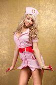 sexy blonde woman in seductive pink nurse costume on golden background