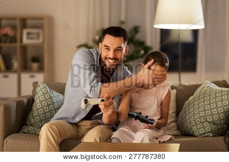 poster of family, gaming and entertainment concept - happy father and little daughter with gamepads playing vi