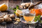 Ginger Tea Honey Lemon And Mint Leaves On Wooden Table poster