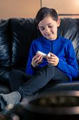 8 Year Old Boy Wearing Sportive Clothing Holding An Asthma Inhaler Sitting In Sofa. Concepts : Healt poster