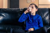 8 Year Old Boy Wearing Sportive Clothing Inhaling With An Asthma Inhaler Sitting In Sofa. Concepts : poster