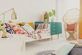 Golden Lamp On Nightstand In Boho Girls Bedroom With Colorful Bedding On Bed, Green Wooden Cabinet  poster