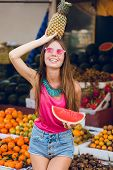 Summer Fashionable Girl Enjoying On Market On Tropical Fruits Background. She Holds Ananas On Head A poster