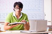 Young male student chemist in front of periodic table  poster