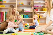 Group Of Babies In Nursery. Nursery Teacher And Assistant Play With Kids On Cosy Rug poster