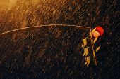 Red Traffic Signal In Dark Time Close Up. Traffic Light At Strong Snowfall. Huge Snowflakes Above Ro poster