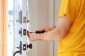 Worker Installing Or Repairing New Lock Handyman Repair The Door Lock poster