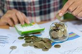Woman Hand Putting Coinin The Glass Jar. Saving Money Wealth And Financial Concept, Personal Finance poster