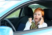 Red-Haired Woman With Mobile-Phone In A Car.