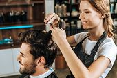 Smiling Young Hairdresser Cutting Hair To Handsome Happy Man In Beauty Salon poster