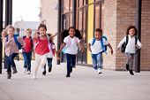 A group of smiling multi-ethnic school kids running in a walkway outside their infant school buildin poster
