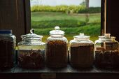 Traditional Thai Dried Medicinal, Natural Herbs Assortment Stored In Glass Jars On Shelf Next To Woo poster