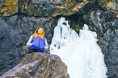 Freedom Traveler Woman Standing. Female Hiking Around Mountains And Stands Behind A Frozen Waterfall poster