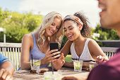 Two young women looking at smart phone and smiling sitting at table outdoor. Happy multiethnic girls poster