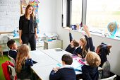 Female primary school teacher standing in classroom and schoolchildren sitting at table raising thei poster
