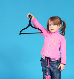 stock photo of clothes hanger  - The child keeps clothes hanger blue background - JPG