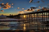 picture of mile  - The sun is setting into the Pacific Ocean behind the wooden Oceanside Pier - JPG