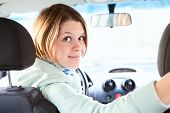 Joyful Woman Inside Of Car Looking Back From Driver Seat