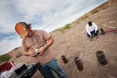 stock photo of crew cut  - Two special effects workers setting up pyrotechnics in desert - JPG