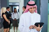 saudi arabian businessman using tablet computer in modern office