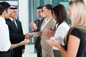 foto of applause  - young translator introducing arab businessman to group of businesspeople - JPG