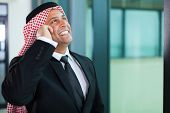 cheerful muslim businessman talking on cell phone and looking up
