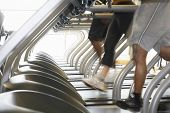 stock photo of treadmill  - Low section of people running on treadmills in health club - JPG