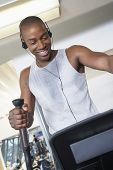 Happy African American man on elliptical machine while listening music at gym
