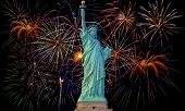 picture of firework display  - Colorful fireworks on black sky with statue of liberty - JPG