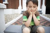 Sad little boy with hands on chin sitting on front steps of house