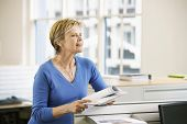 Middle aged businesswoman with documents looking away in office