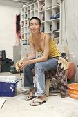 Portrait of young female interior decorator sitting on stool in work site