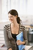Happy young businesswoman with file leaning on cubicle