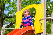 Little girl on a climbing frame in summer slide down