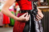 Traditional clothes - young woman is buying Tracht or dirndl in a shop, she has to try it on before