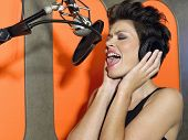 Closeup of a female singer recording a track in a studio