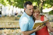 Happy couple reading a guidebook outdoors
