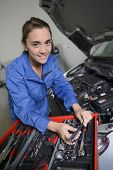 Student girl in mechanics working on car engine