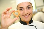 Portrait of young pastry cook holding cookie