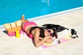 foto of sunbathing  - Woman and dog relaxing and sunbathing together on funny summer at swimming pool - JPG