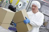 White male  worker working on packing line in factory