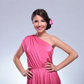 young beauty woman wearing a cute pink dress and a rose in her hair smiles for the camera with her hands on her hips. on a light gray background