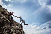 stock photo of teamwork  - Man giving helping hand to friend to climb mountain rock cliff - JPG