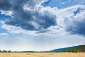 Beautiful clouds in blue sky over field steppe landscape horizon in Siberia.