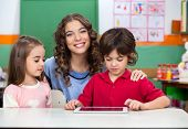 Portrait of young teacher with children using digital tablet at classroom desk