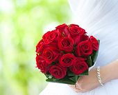 Bride Holds Bouquet Of Red Roses