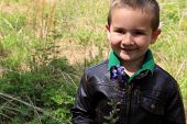 Young adorable smiling boy in grassy field