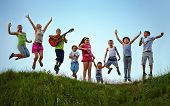 image of candid  - group of happy kids jumping on summer field - JPG